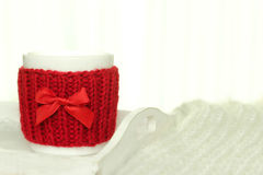 Mug of hot drink with red knitted warmer Stock Photos