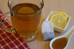 Glass mug of green tea with lemon and honey. Mug of hot tea with lemon slices and honey on a wood problme Stock Image
