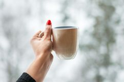 Mug In The Hand On Snow Royalty Free Stock Photography