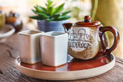 Mug and a Jug in plate on a wooden table Royalty Free Stock Photos