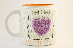 Mug with knitted hot water bottle decorated with  heart Stock Photography