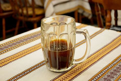 Mug of kvass. Close-up of a half-filled mug of kvass on a stripy cloth Stock Image