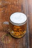 Mug, lager, beer, foam, wooden table, pub, Oktoberfest, German b royalty free stock photos