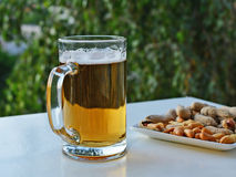 Mug of light beer and peanuts on the table Stock Photography