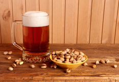 Mug with light beer and pistachios Stock Photos