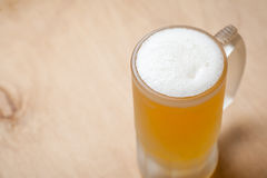 Mug of light beer on wood Stock Images
