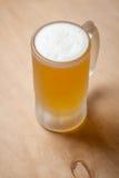 Mug of light beer on wood Royalty Free Stock Image