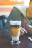 Mug with makiato. Transparent mug with coffee machiato is on the table Stock Photo