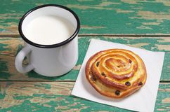 Mug of milk and bun Stock Photos