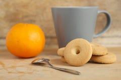 Mug of milk with cookies and orange Stock Image