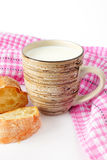 Mug with milk and freshly baked bread. Milk in a ceramic mug, freshly baked bread and pink kitchen towel. white background Royalty Free Stock Photos