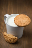 Mug of milk and oat cookies on a wooden background Royalty Free Stock Photography