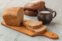 Mug with milk and rye bread Stock Images