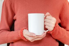 Mug Mockup. Women`s Hands Holding Mug With Blank Space For Your Text Or Promotional Content Stock Photo