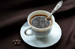 A mug of morning coffee. Fragrant. White mug of morning coffee. On a saucer with spoon. On a dark background royalty free stock photos
