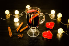 Mug of mulled wine with spices, candles in the shape of a heart, cinnamon sticks, star anise. Illumination of rattan lanterns on a Stock Photo