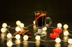 Mug of mulled wine with spices, candles in the shape of a heart, cinnamon sticks, star anise. Illumination of rattan lanterns on a Stock Photography