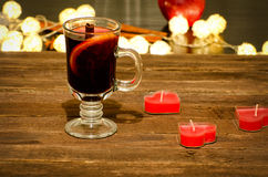 Mug of mulled wine with spices, candles in the shape of a heart on a wooden table. Garland of lanterns in the background Royalty Free Stock Photos