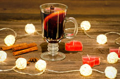 Mug of mulled wine with spices, candles in the shape of a heart on a wooden table, a garland of lanterns. Cinnamon sticks, anise Royalty Free Stock Image