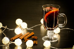 Mug of mulled wine with spices, cinnamon sticks, star anise. Illumination of rattan lanterns on a black wooden table Stock Photos