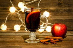 Mug of mulled wine with spices close up. Apple, cinnamon sticks and star anise on a wooden table, lanterns in the background Stock Photography