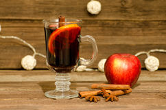 Mug of mulled wine with spices close up. Apple, cinnamon sticks and star anise on a wooden table, lanterns in the background Stock Images