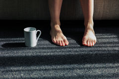Mug next to feet of woman at home Stock Photography
