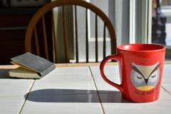 Mug and notebook on a table stock photography