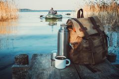 Free Mug Of Coffee Or Tea, Backpack Of Traveller And Thermos On Wooden Pier On Tranquil Lake. A Fisherman On Rubber Boat. Royalty Free Stock Photos - 161620318