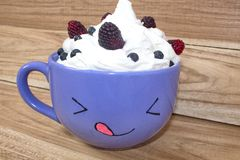 A mug with painted faces, whipped cream and berries stands on a wooden shelf. Vanilla mousse with blackberries and blueberries. Still life stock images