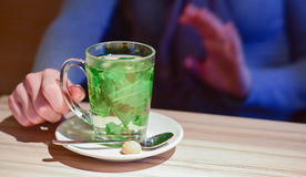 Mug of peppermint tea. Mug of fresh peppermint tea in a saucer with spoon and sugar lump (or sweet) placed on a wooden table (beside a customer stock photo