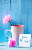 Mug with pink roses on blue wood background with good morning Stock Image