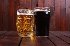 Mug and pint of beer. Classic mug and pint glasses full of light and dark beer standing on a wooden table royalty free stock image