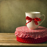 Mug with ribbon on round box Royalty Free Stock Images