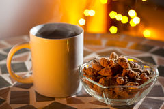 A mug and roasted almonds. A mug of tea with sugar cinnamon coated almonds with christmas lights in the back Stock Photography