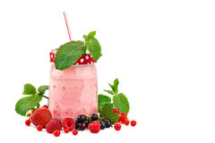 Mug smoothies and ripe berries on a white background. An isolated object stock image