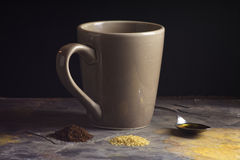 Mug And Spoon With Coffee Ingredients On Gray Slate. Mug and spoon of honey behind raw sugar and coffee grounds on light gray slate in front of black background Stock Images