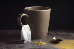 Mug And Spoon With Tea Ingredients On Gray Slate. Mug and spoon of honey behind raw sugar and tea bag on light gray slate in front of black background Royalty Free Stock Photo