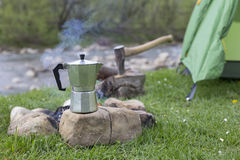 Mug stands on a log near the fire at a campsite. Stock Photos