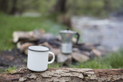 Mug stands on a log near the fire at a campsite. Royalty Free Stock Photography