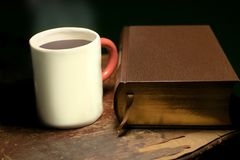 A mug with steaming hot tea or coffee placed next to a big leather-bound book, on an old and worn wooden table royalty free stock photos