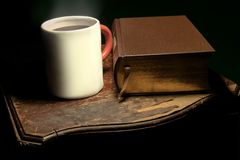 A mug with steaming hot tea or coffee placed next to a big leather-bound book, on an old and worn wooden table royalty free stock images