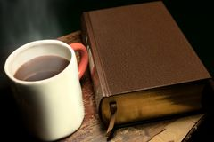 A mug with steaming hot tea or coffee placed next to a big leather-bound book, on an old and worn wooden table royalty free stock photo