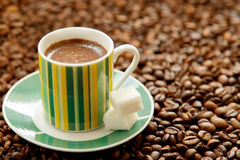 Mug of strong coffee and sugar scattered on coffee beans. Mug of strong coffee and sugar Royalty Free Stock Photo