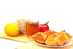 Mug of tea, cakes on a plate, lemon, apple with green leaf and s. Mug of tea cakes on a plate, lemon, apple with green leaf and sugar in a bowl on a bed of reeds Royalty Free Stock Photos