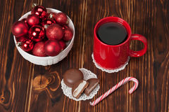Mug Of Tea Or Coffee. Sweets. Christmas. Decorations. Red Balls And Bells. Wooden Background Stock Photography