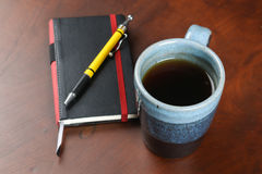Mug of tea and coffee on wood table with notebook and pen Stock Images