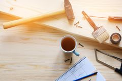 Mug of tea, drawings and construction tools for building a house or apartment renovation, on a wooden table. The workplace of the stock image