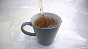 Mug of tea filled in slow motion stock footage