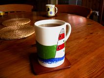 Mug with tea in the foreground on a round table royalty free stock image